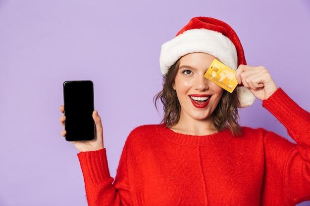 Porträt einer glücklichen jungen frau, die weihnachtshut trägt, lokalisiert über lila wand unter verwendung des mobiltelefons, das kreditkarte hält.