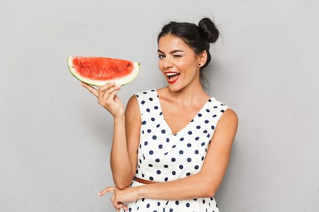 Porträt einer glücklichen jungen frau im sommerkleid lokalisiert, wassermelonenscheibe haltend, zwinkernd