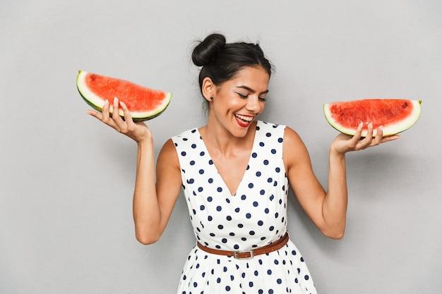 Porträt einer glücklichen jungen frau im sommerkleid lokalisiert, zwei wassermelonenscheiben haltend