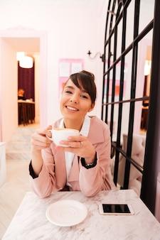 Porträt einer glücklichen jungen frau in der rosa jacke, die kaffee trinkt