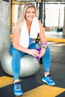 Porträt einer glücklichen jungen frau mit der wasserflasche, die auf eignungsball sitzt