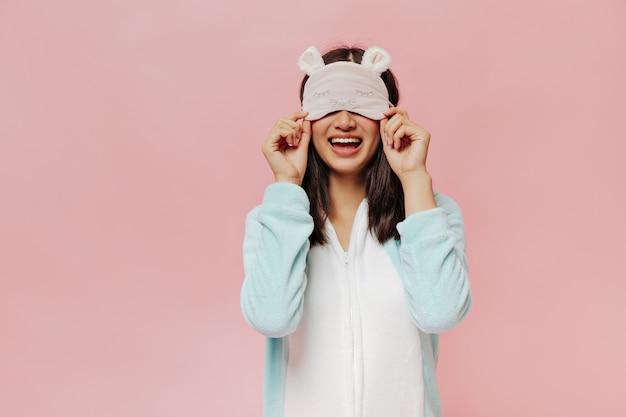 Porträt einer glücklichen jungen frau zieht süße schlafmaske an