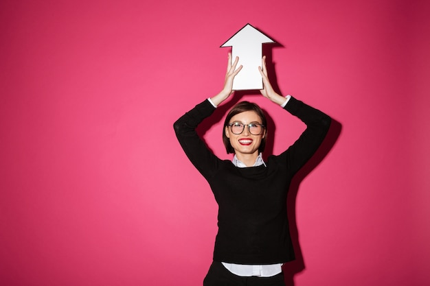 Porträt einer glücklichen jungen geschäftsfrau, die papierpfeilzeichen hält