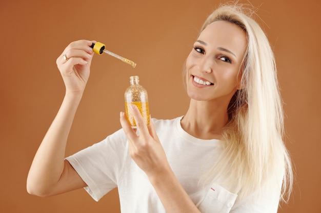 Porträt einer glücklichen jungen hübschen frau, die eine flasche serum oder öl zur befeuchtung und konditionierung des haares zeigt