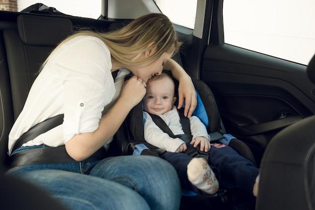 Porträt einer glücklichen jungen mutter, die mit ihrem baby auf dem rücksitz sitzt
