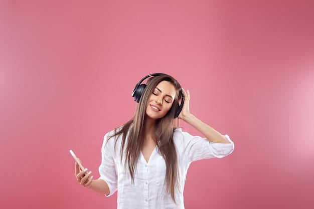 Porträt einer glücklichen jungen schönen frau, die lokal über rosa wand aufwirft