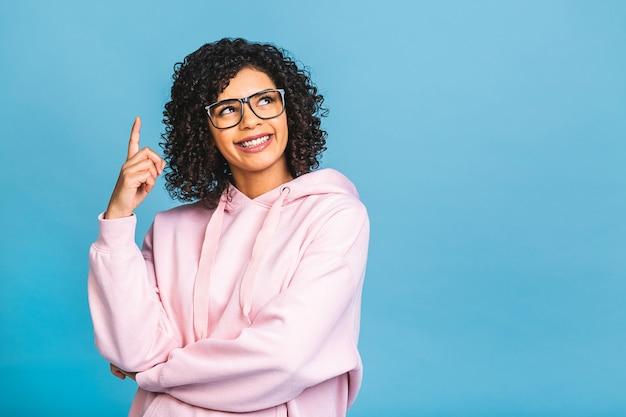 Porträt einer glücklichen jungen schwarzen afroamerikanerfrau, die finger weg auf kopienraum lokalisiert über blauem hintergrund zeigt.