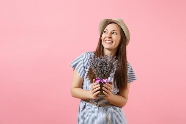 Porträt einer glücklichen jungen zarten frau in blauem kleid, hut, der einen strauß schöner lila lavendelblüten hält, einzeln auf hellem rosafarbenem hintergrund. feiertagskonzept zum internationalen frauentag.