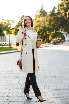 Porträt einer glücklichen kaukasischen frau mit mantel, die kaffee zum mitnehmen trinkt und beim gehen auf der stadtstraße auf dem handy spricht