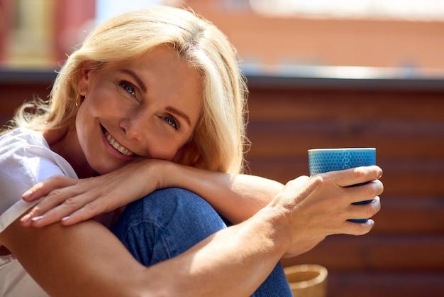 Porträt einer glücklichen kaukasischen frau mittleren alters mit einer tasse kaffee, die in die kamera schaut und lächelt, während sie auf einem sonnigen balkon sitzt. menschen, die zeit zu hause verbringen