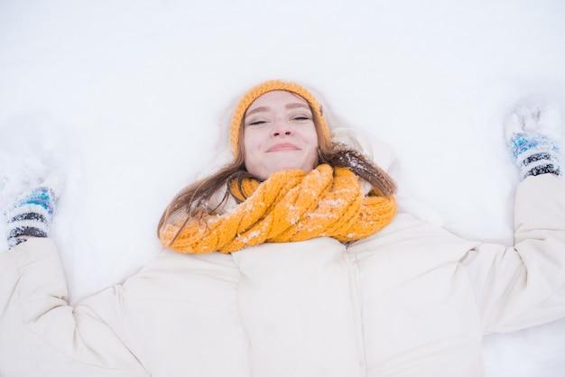 Porträt einer glücklichen lächelnden frau, die auf dem schnee an einem verschneiten wintertag liegt