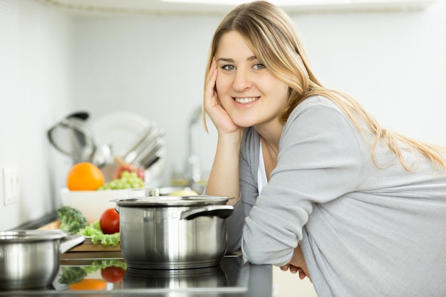 Porträt einer glücklichen lächelnden frau, die auf küche aufwirft und suppe kocht