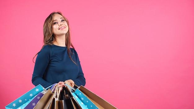 Porträt einer glücklichen lächelnden frau, die ein bündel von paketen nach dem einkaufen hält