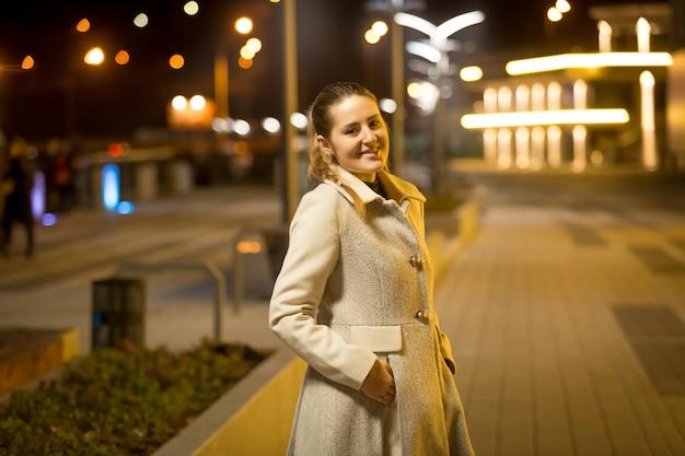 Porträt einer glücklichen lächelnden frau, die nachts auf der straße geht