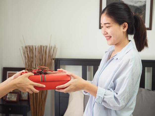 Porträt einer glücklichen lächelnden frau nehmen eine geschenkbox