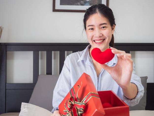Porträt einer glücklichen lächelnden frau öffnen eine geschenkbox auf bett