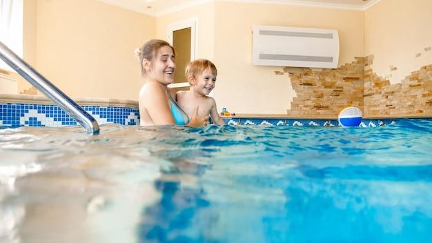 Porträt einer glücklichen lächelnden mutter mit dem 3 jahre alten kleinen sohn, der im pool im fitnessstudio schwimmt