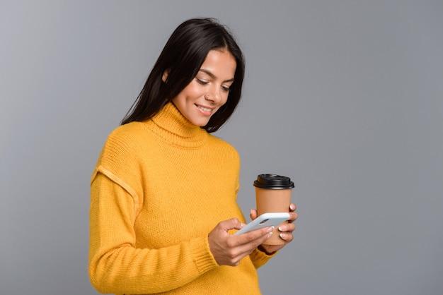 Porträt einer glücklichen lässigen jungen frau lokalisiert über graue wand, kaffee zum mitnehmen haltend, unter verwendung des mobiltelefons