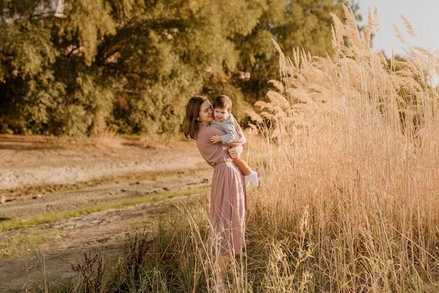 Porträt einer glücklichen liebevollen mutter, die ihren kleinen sohn im sonnigen park in der nähe des flusses umarmt.