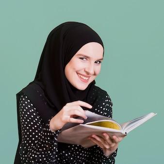Porträt einer glücklichen moslemischen frau, die in der hand buch hält