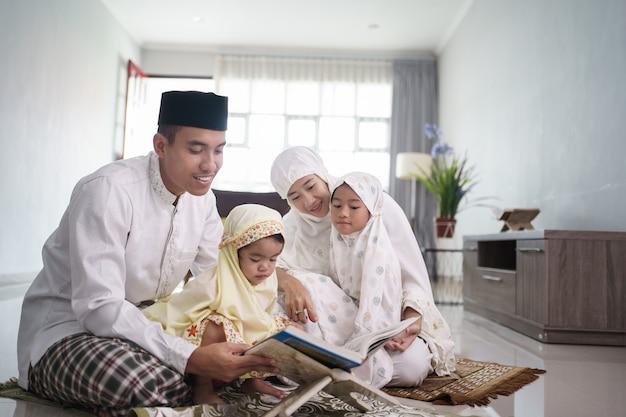 Porträt einer glücklichen muslimischen familie mit kindern, die koran lesen und zusammen zu hause beten