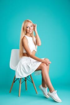 Porträt einer glücklichen netten frau, die auf dem stuhl lokalisiert auf dem blauen hintergrund sitzt