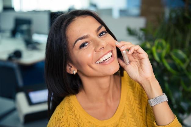 Porträt einer glücklichen netten geschäftsfrau, die im büro am telefon spricht