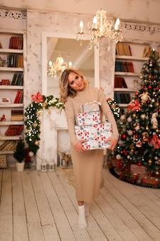 Porträt einer glücklichen niedlichen frau, die viele geschenkboxen auf dem hintergrund eines weihnachtsbaumes hält