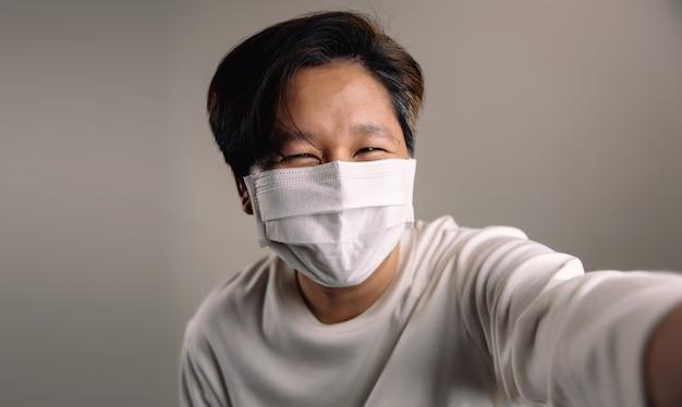 Porträt einer glücklichen person, die eine chirurgische maske trägt und selfie gegen die weiße wand nimmt