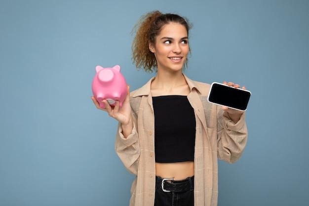 Porträt einer glücklichen, positiv lächelnden jungen, attraktiven, brünetten, lockigen frau mit aufrichtigen emotionen, die ein stilvolles beigefarbenes hemd einzeln auf blauem hintergrund mit kopienraum trägt, hält rosa schweinegeld