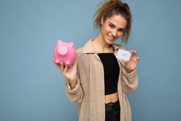 Porträt einer glücklichen, positiv lächelnden jungen, attraktiven, brünetten, lockigen frau mit aufrichtigen emotionen, die ein stylisches beigefarbenes hemd trägt, isoliert über blauer wand mit freiem platz, hält rosa schwein-münzbank a