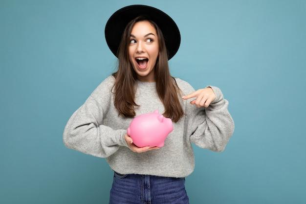 Porträt einer glücklichen, positiv überraschten jungen, schönen brünetten frau, die einen stilvollen grauen pullover trägt und