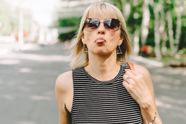 Porträt einer glücklichen reifen erwachsenen frau, die gesichter macht und ihre zunge herausstreckt senior zeigt ihre zunge