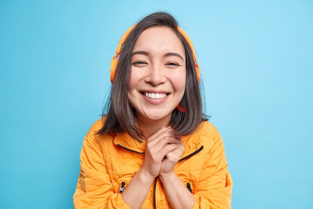 Porträt einer glücklichen schönen asiatischen frau hält die hände zusammen und lächelt im großen und ganzen genießt guten sound mit modernem headset hört musik aus der playlist trägt orangefarbene jacke isoliert über blauer wand