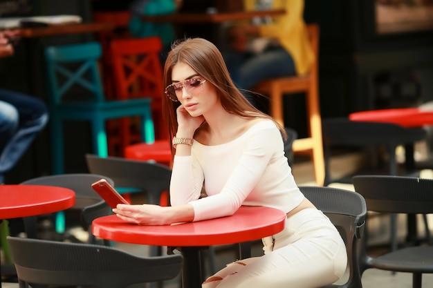 Porträt einer glücklichen schönen brünette, die in einem europäischen café sitzt