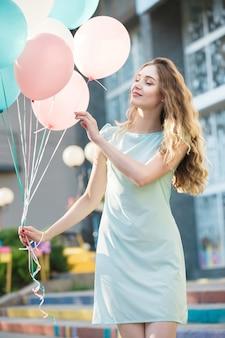 Porträt einer glücklichen schönen frau mit fliegenden bunten luftballons in der stadt