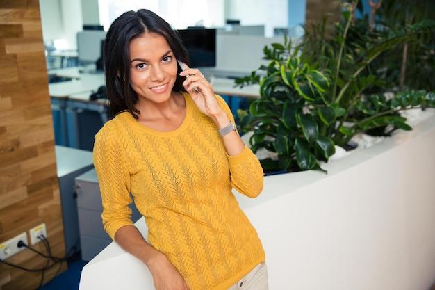 Porträt einer glücklichen schönen geschäftsfrau, die im büro am telefon spricht