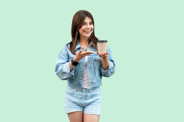 Porträt einer glücklichen, schönen jungen brünetten frau im lässigen denim-stil, die eine einwegschale heißes getränk zeigt und die kamera mit einem zahnigen lächeln betrachtet. studioaufnahme, auf grünem hintergrund isoliert.