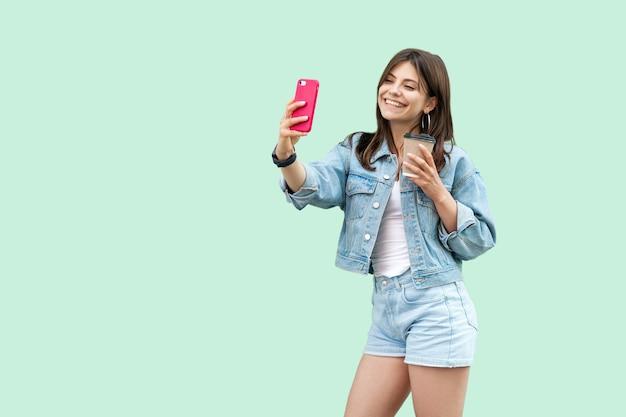 Porträt einer glücklichen schönen jungen brünetten frau im lässigen denim-stil, die mobiles smartphone und einwegbecher getränk steht und hält, zahniges lächeln. studioaufnahme, auf grünem hintergrund isoliert.