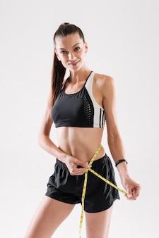 Porträt einer glücklichen sportlerin, die ihre taille misst