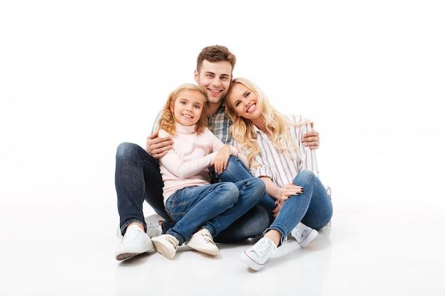 Porträt einer glücklichen zusammen sitzenden und umarmenden familie