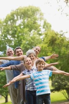 Porträt einer großfamilie, die hände am park ausdehnt