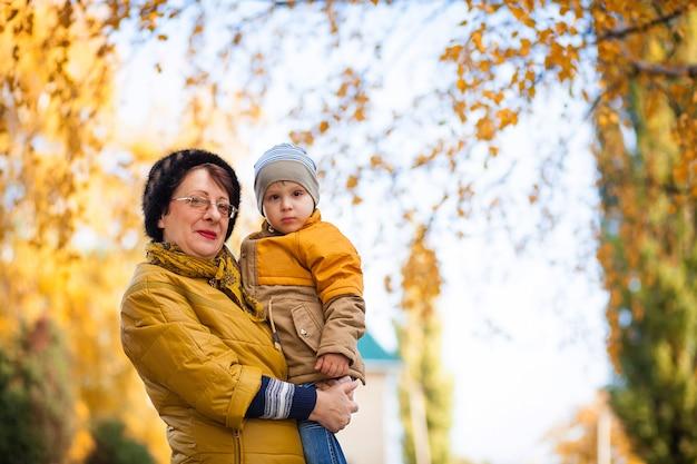Porträt einer großmutter mit einem enkel im arm für einen spaziergang im herbstpark