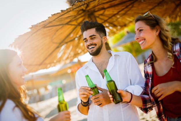 Porträt einer gruppe junger freunde, die eine party am strand veranstalten