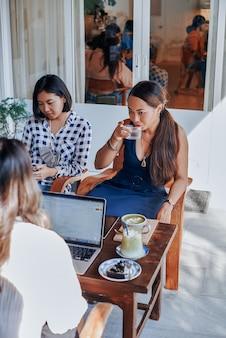 Porträt einer gruppe von drei asiatischen geschäftsfrauen, die einige ideen planen und diskutieren, die am tisch in einem modernen büroraum sitzen.