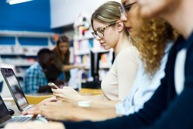 Porträt einer gruppe von freunden, die in einer universitätsbibliothek studieren.