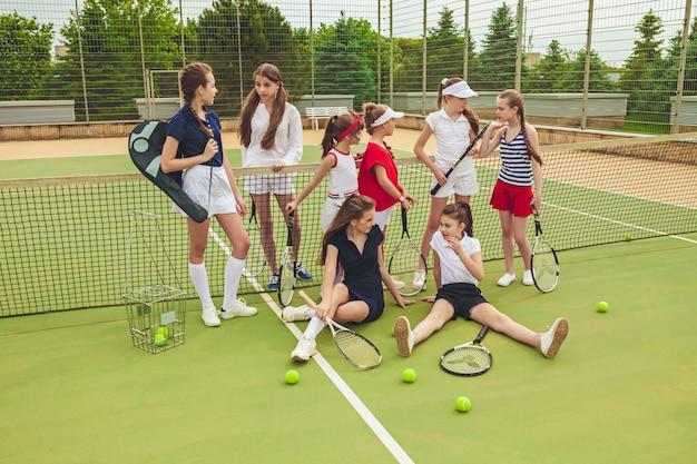 Porträt einer gruppe von mädchen als tennisspieler, die tennisschläger halten