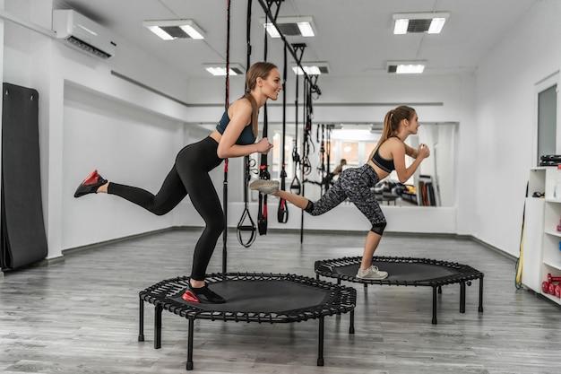 Porträt einer gruppe zwei mädchen in gymnastik-fitness-trampolinen in der turnhalle