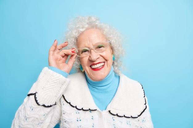 Porträt einer gut aussehenden, fröhlichen, grauhaarigen großmutter, die zahnig lächelt, hält die hand am brillenrand hat einen gepflegten teint, faltige sünde, gekleidet in einen weißen pullover jump