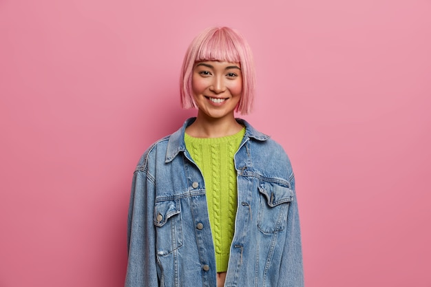 Porträt einer gut aussehenden jungen frau mit rosa frisur, lächelt sanft, drückt positive gefühle aus, trägt einen grünen, kurz geschnittenen pullover, eine jeansjacke und posiert im innenbereich. menschen, jugend, glückliche gefühle konzept